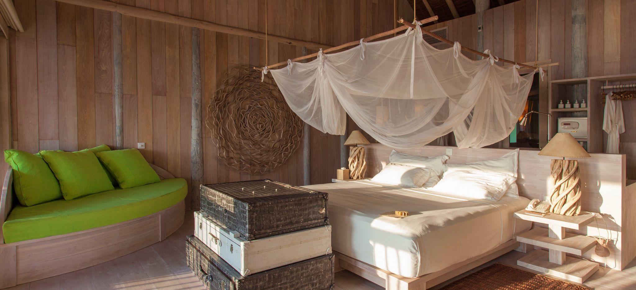 """Ein Schlafzimmer aus hellem Holz, luxuriös und stilvoll eingerichtet. Im Hotel """"Soneva Fushi"""" auf den Malediven."""