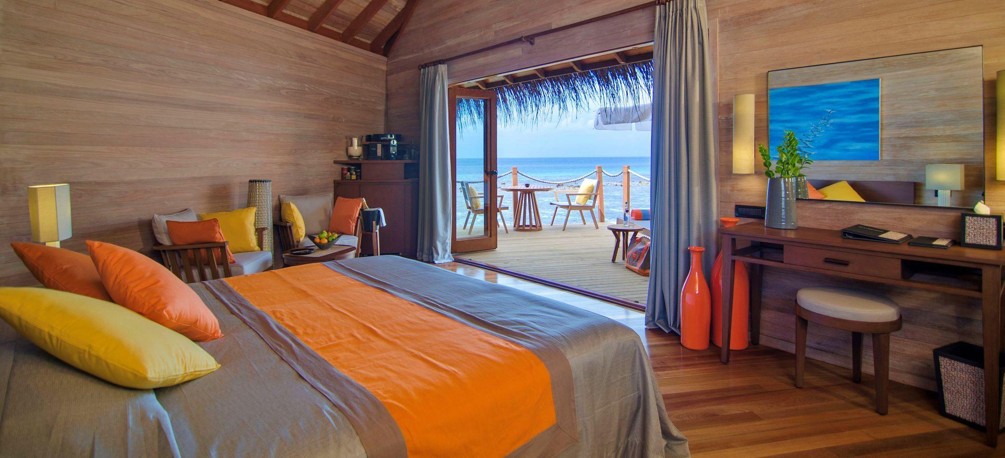 Ein helles Schlafzimmer mit Blick auf die Lagune der Malediveninsel Mirihi