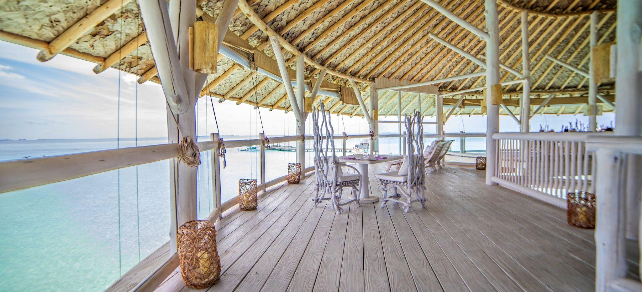 Ein mit weißem, hellen Holz verkleidetes Restaurant mit Blick auf as Meer der Malediven