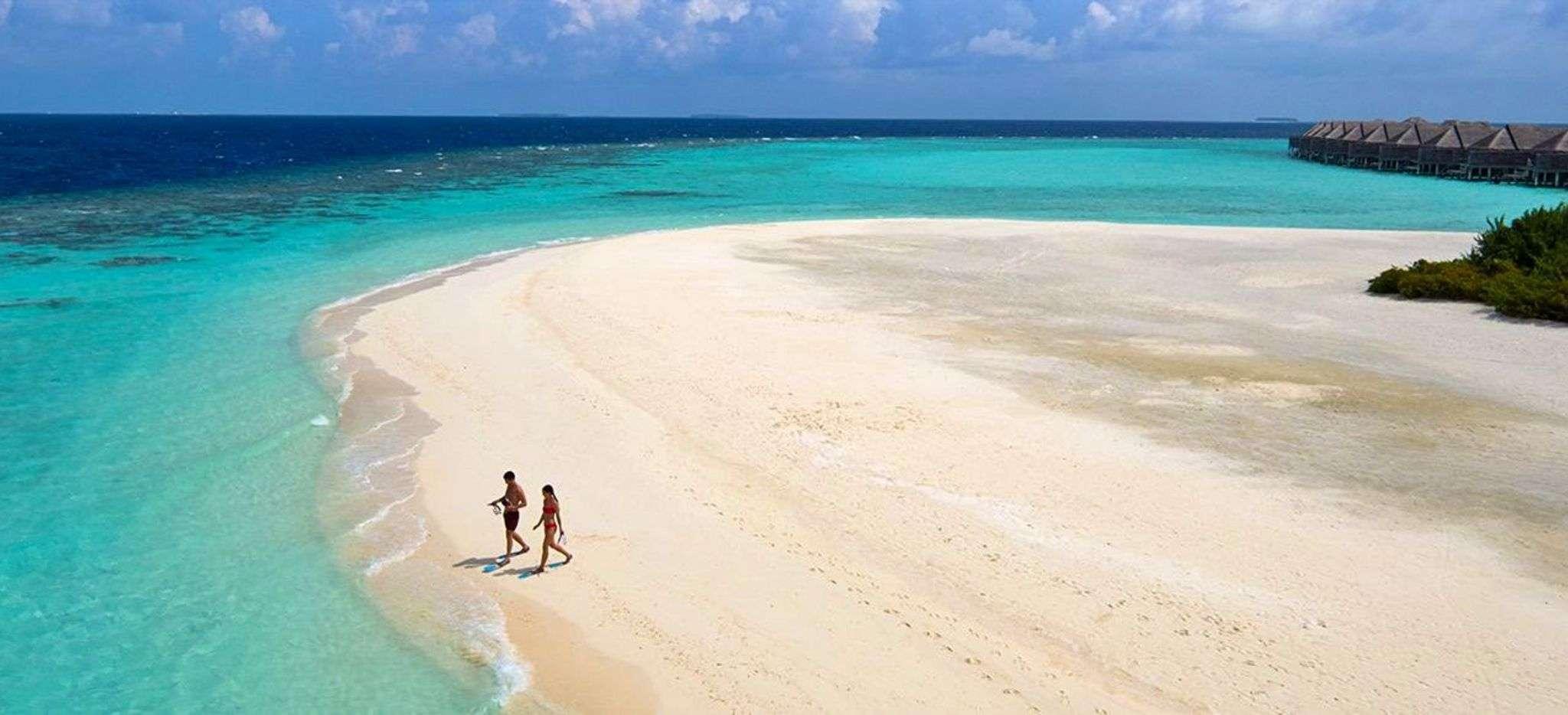 Ein paar spaziert am weißen Sandstrand auf den Malediven