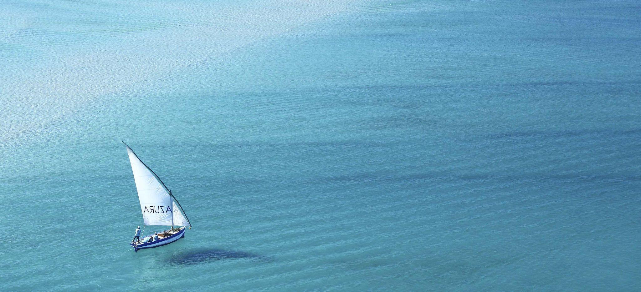 Ein traditionelles Dhow segelt über das Meer vor dem Hotel Azura Benguerra in Mosambik