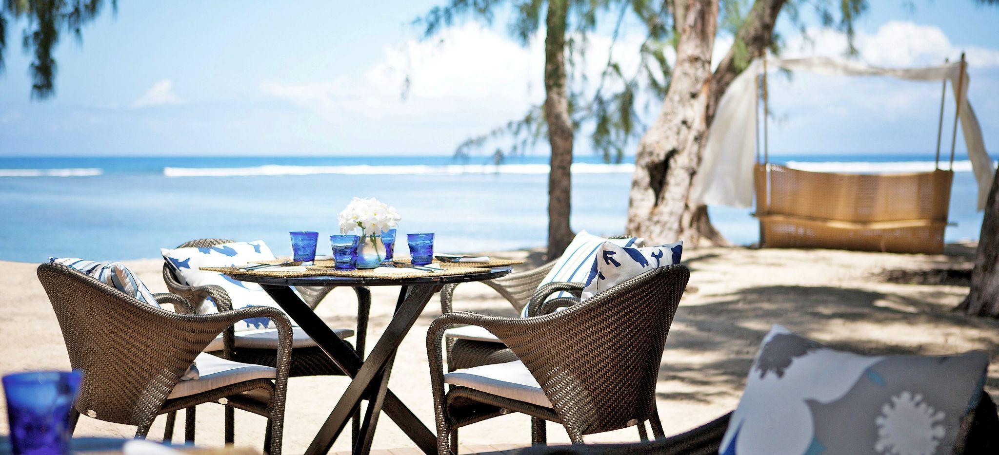 Ein Tisch im Schatten vor dem Strand des Hotels LUX* Saint Gilles