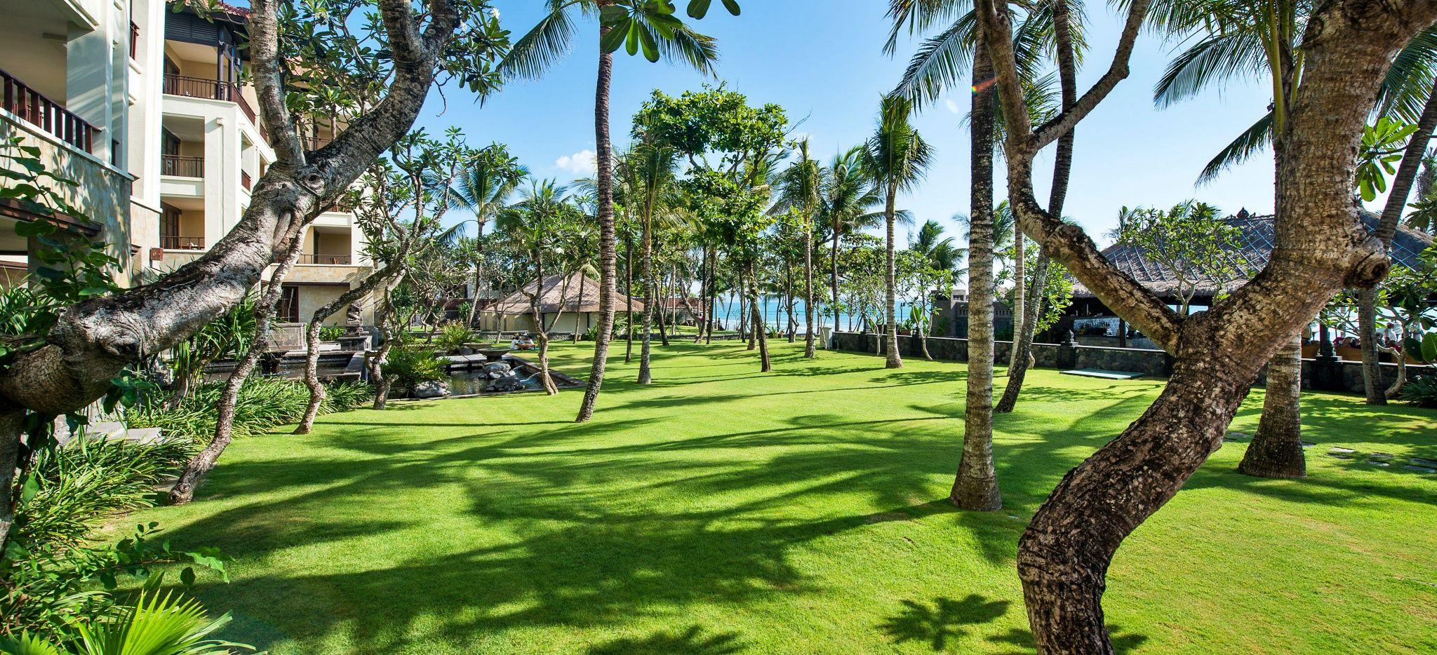 """Ein grüner Englischer Rasen mit Bäumen im Hotel """"The Legian"""""""