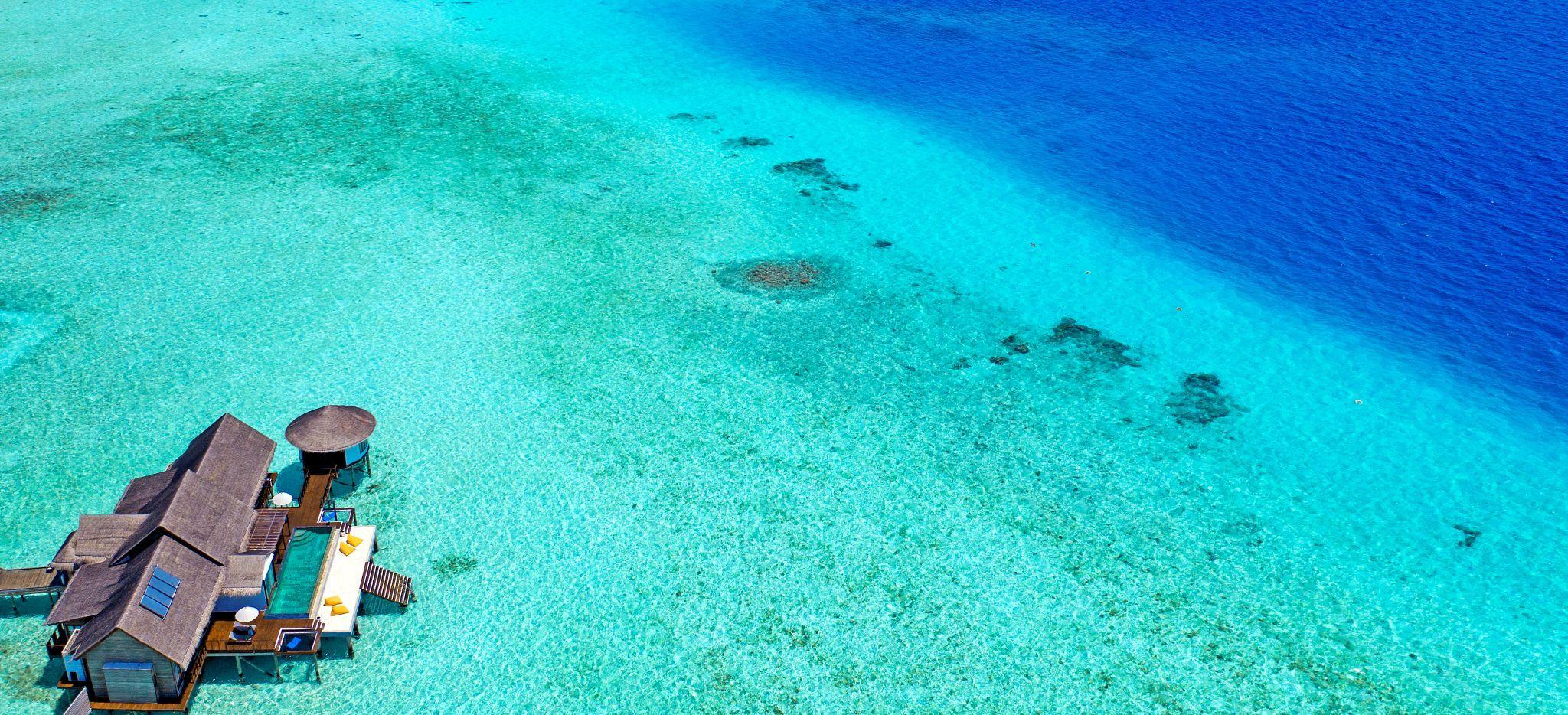 Eine große Wasservilla umgeben von flachem, türkisblauem Meer, vor der Insel Madhoo, Malediven