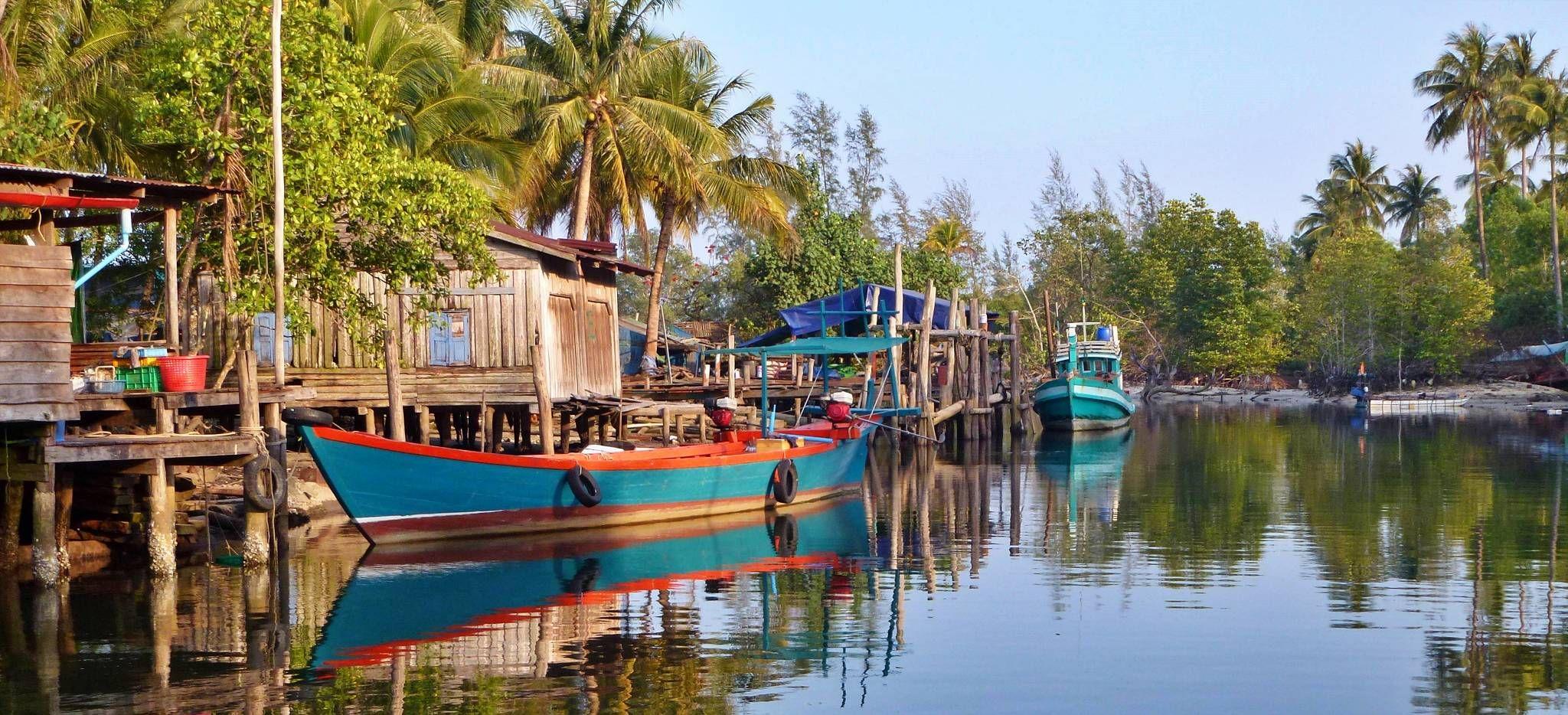Traditionelles Boot und Stelzenhäuser an einem Fluss in Kambodscha