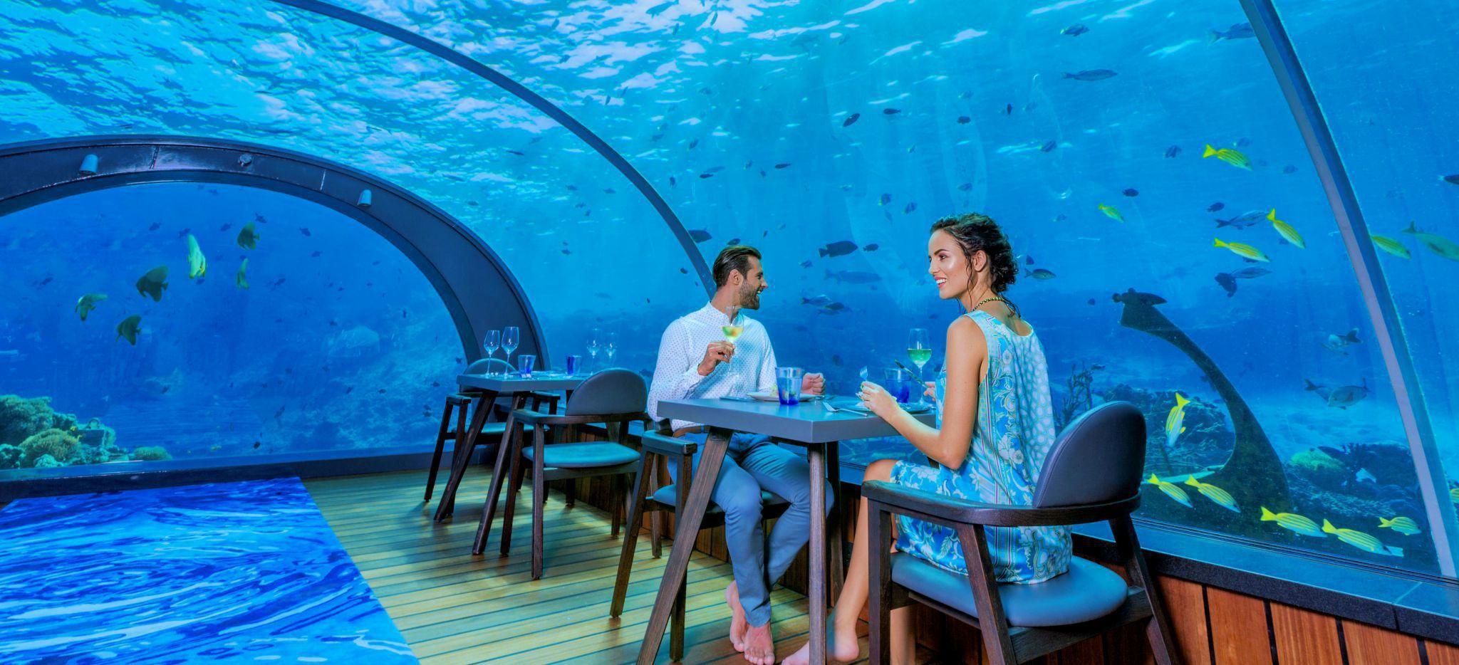 """Ein Paar sitzt staunend in einem Restaurant unter Wasser, """"5.8"""" im Hotel Hurawalhi"""