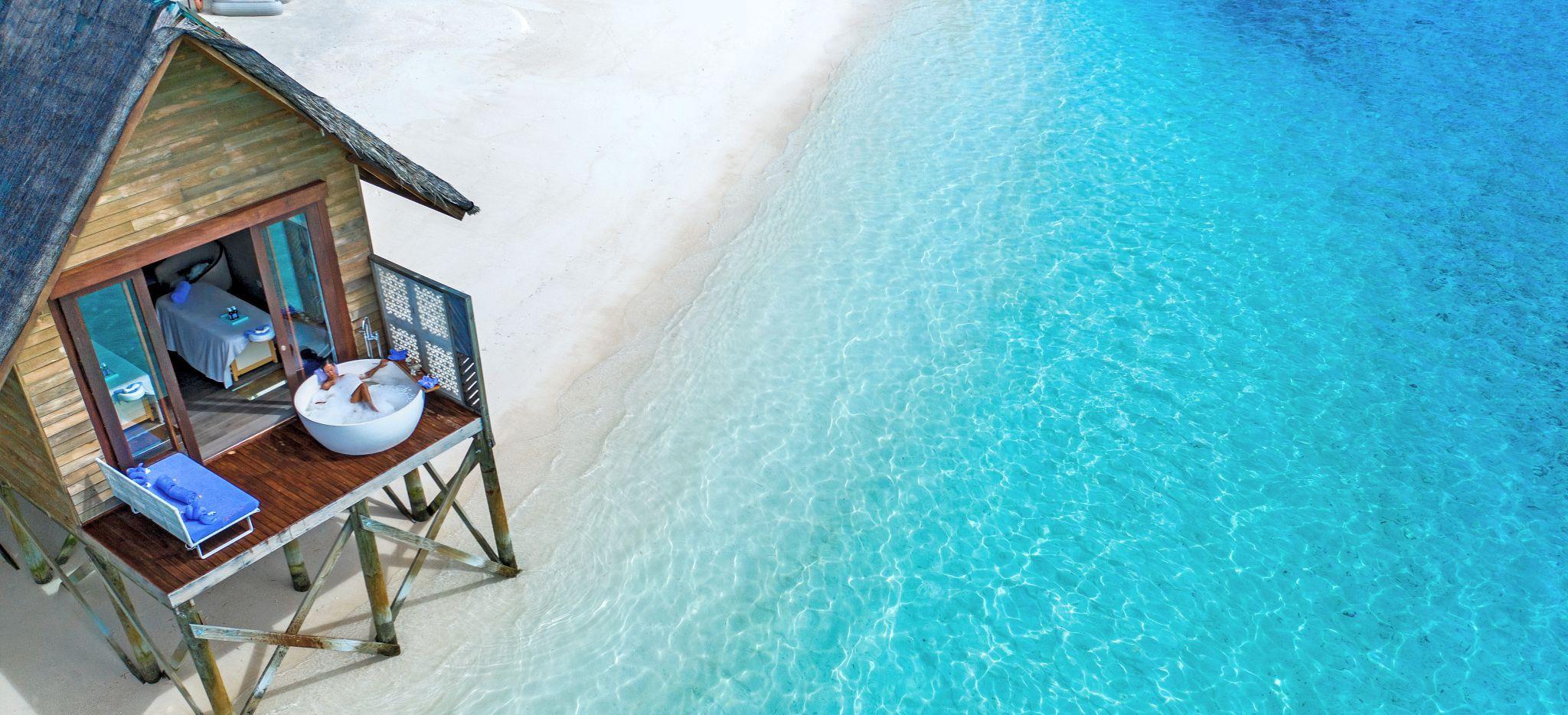 Eine Frau in einer Badewanne vor dem Wellnessbereich des Hotels OZEN auf den Malediven, mit Blick auf das Meer