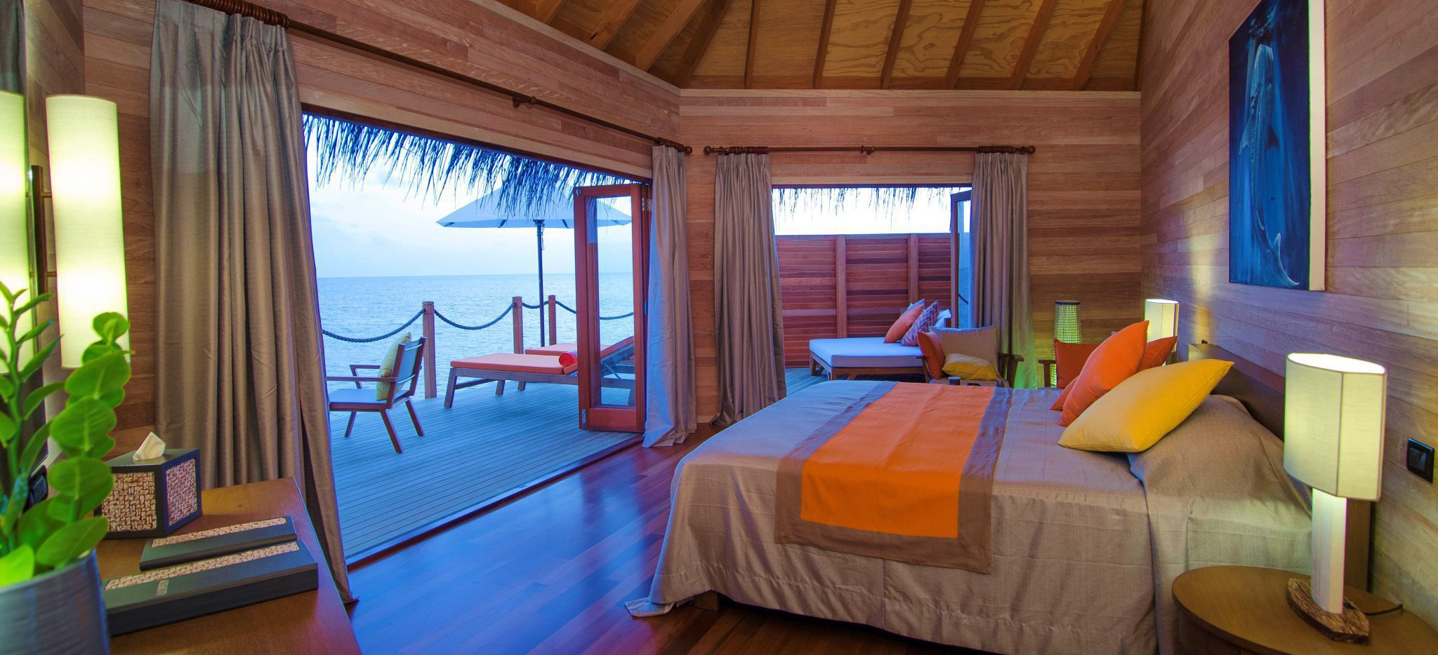 Ein Schlafzimmer aus hellem Holz und viel Orange, mit Blick auf die Lagune der Malediveninsel Mirihi über eine Terrasse