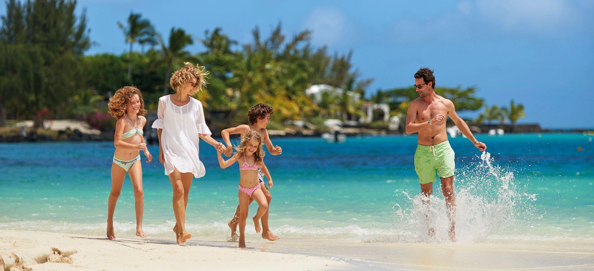 Frau wandert mit Kindern einen Strand entlang, während ein Mann durch das Wasser läuft