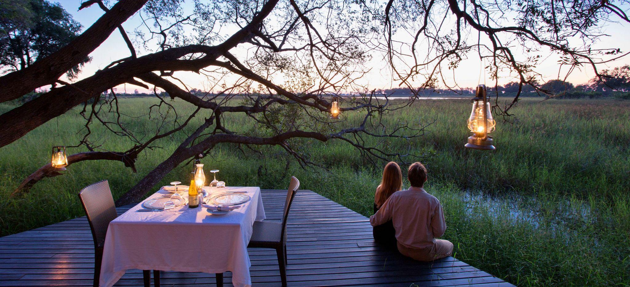 Ein Paar sitzt auf einer Plattform über dem Sumpf des Okavango Delta. Neben Ihnen befindet sich ein Esstisch für zwei.