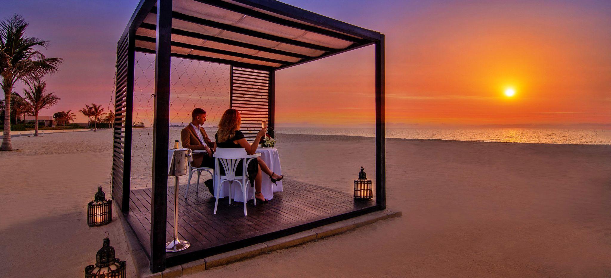 Ein Paar isst in einem Cabana am Strand zu Abend und beobachtet den Sonnenuntergang