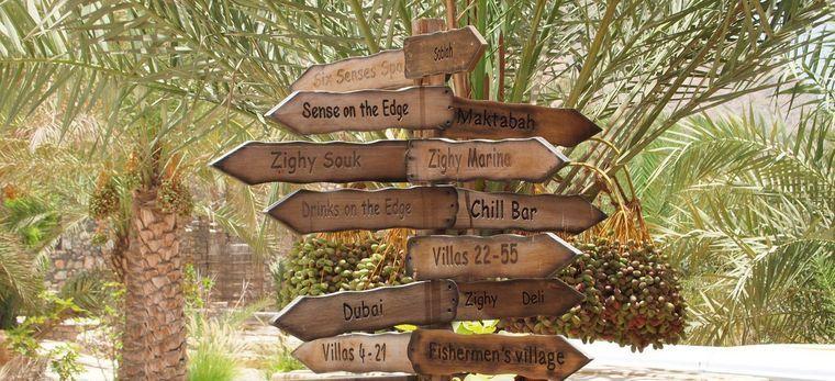 """Hölzerne Schilder im Dattelwald des """"Six Senses Zighy Bay"""" im Oman"""