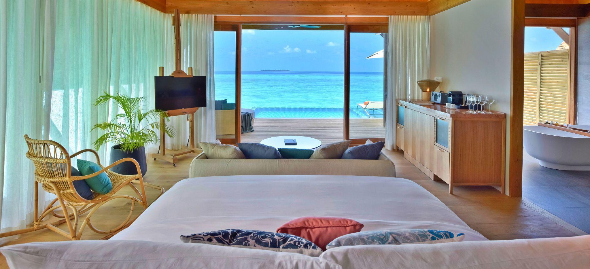 Bett mit Blick auf das Meer in einem Hotelzimmer des Hotels Faarufushi Maldives, auf den Malediven