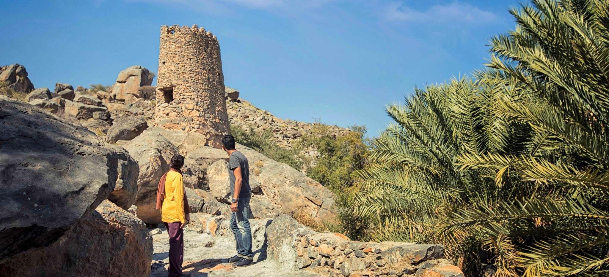 Paar betrachtet einen verfallenen Steinturm auf einem Berg im Dorf Misfat im Oman