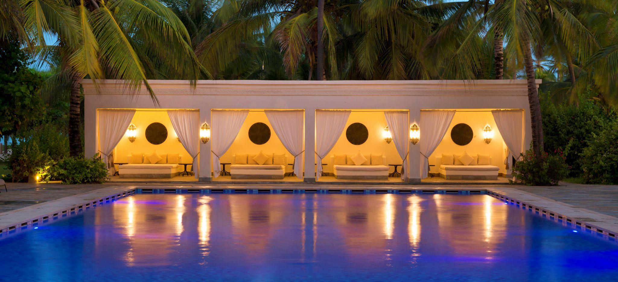 Ein Pool umsäumt von Palmen, mit einem Poolhaus, das wie ein omanischer Palast anmutet
