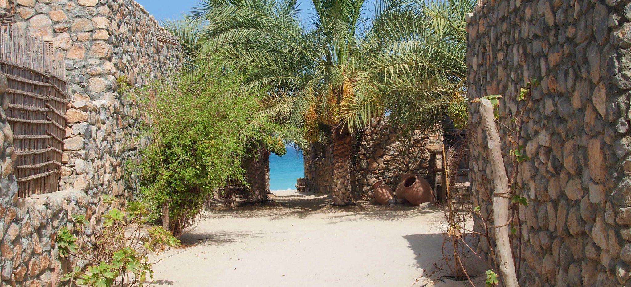 """Weg zwischen steinernen Häusern am Strand im Hotel """"Six Senses Zighy Bay"""" im Oman"""