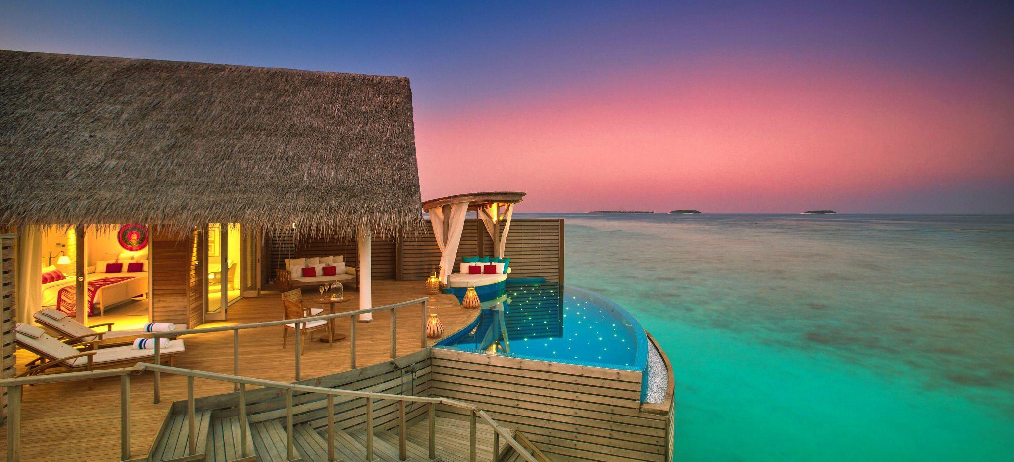 Eine Wasservilla mit privatem Pool vor dem Sonnenuntergang, im Hotel Milaidhoo auf den Malediven