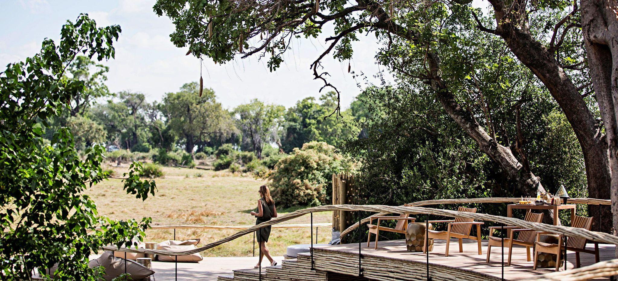 """Eine Frau auf der Terrasse eines der Zimmer der Safari-Lodge """"Little Mombo"""" in Botsuana"""