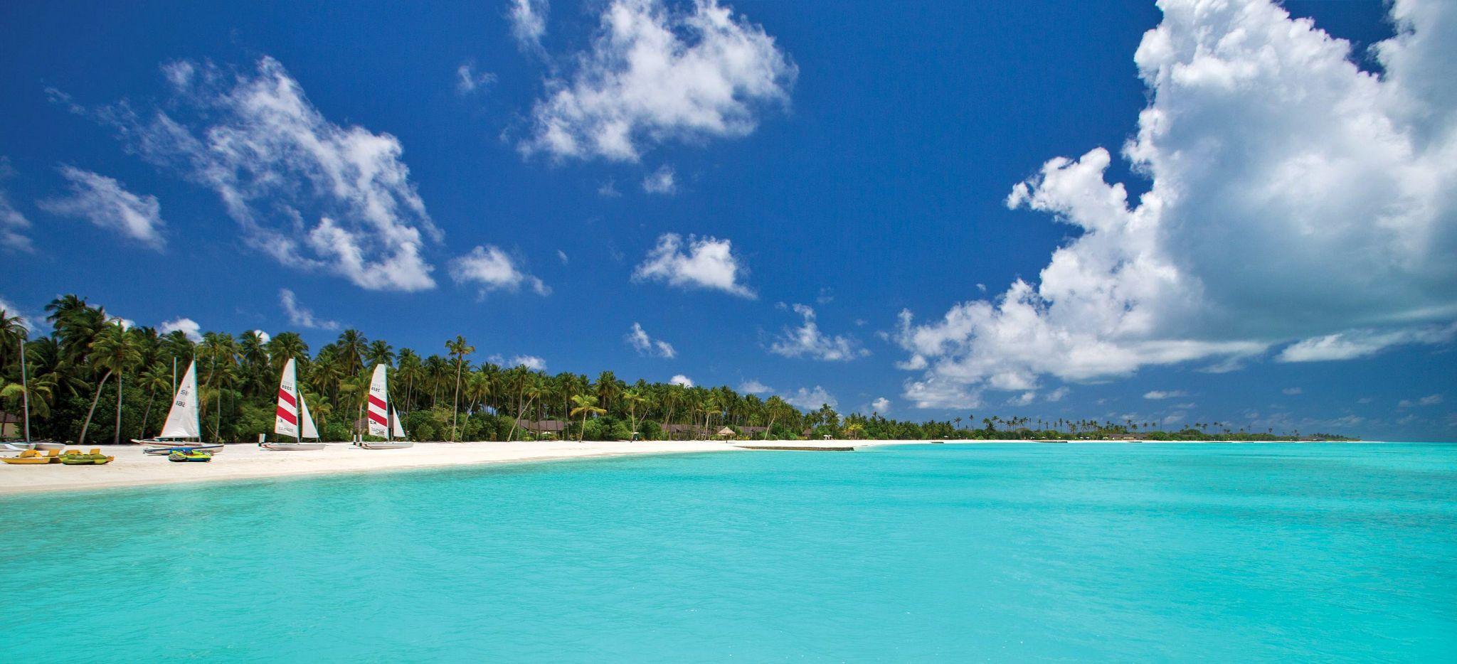 Mehrere Segelboote aufgereit auf einem Strand auf den Malediven. Das Hotel Atmosphere Kanifushi