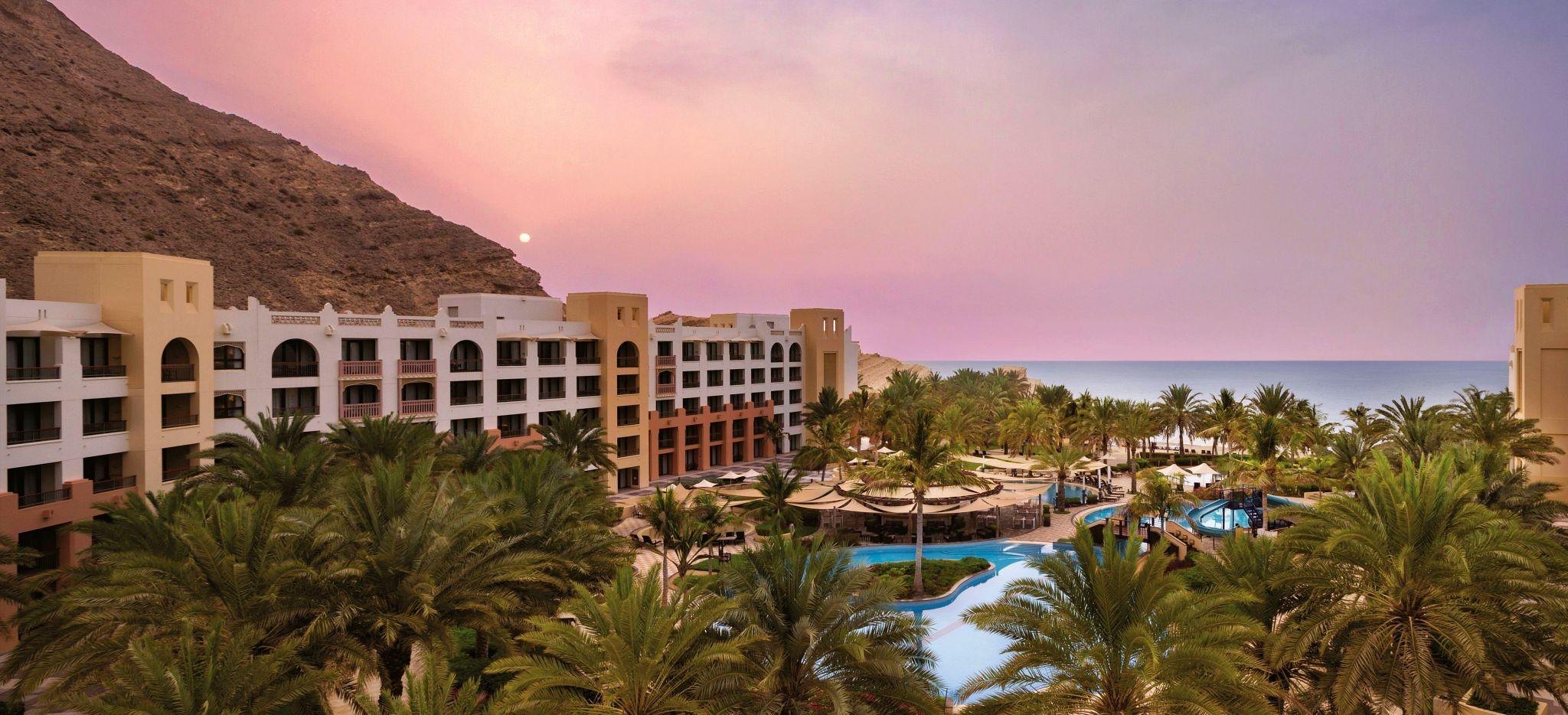 Luftaufnahme von Hotel und Sonnenuntergang im Shangri-La Barr Al Jissah Al Bandar Resort nahe Maskat, Oman, gespiegelt