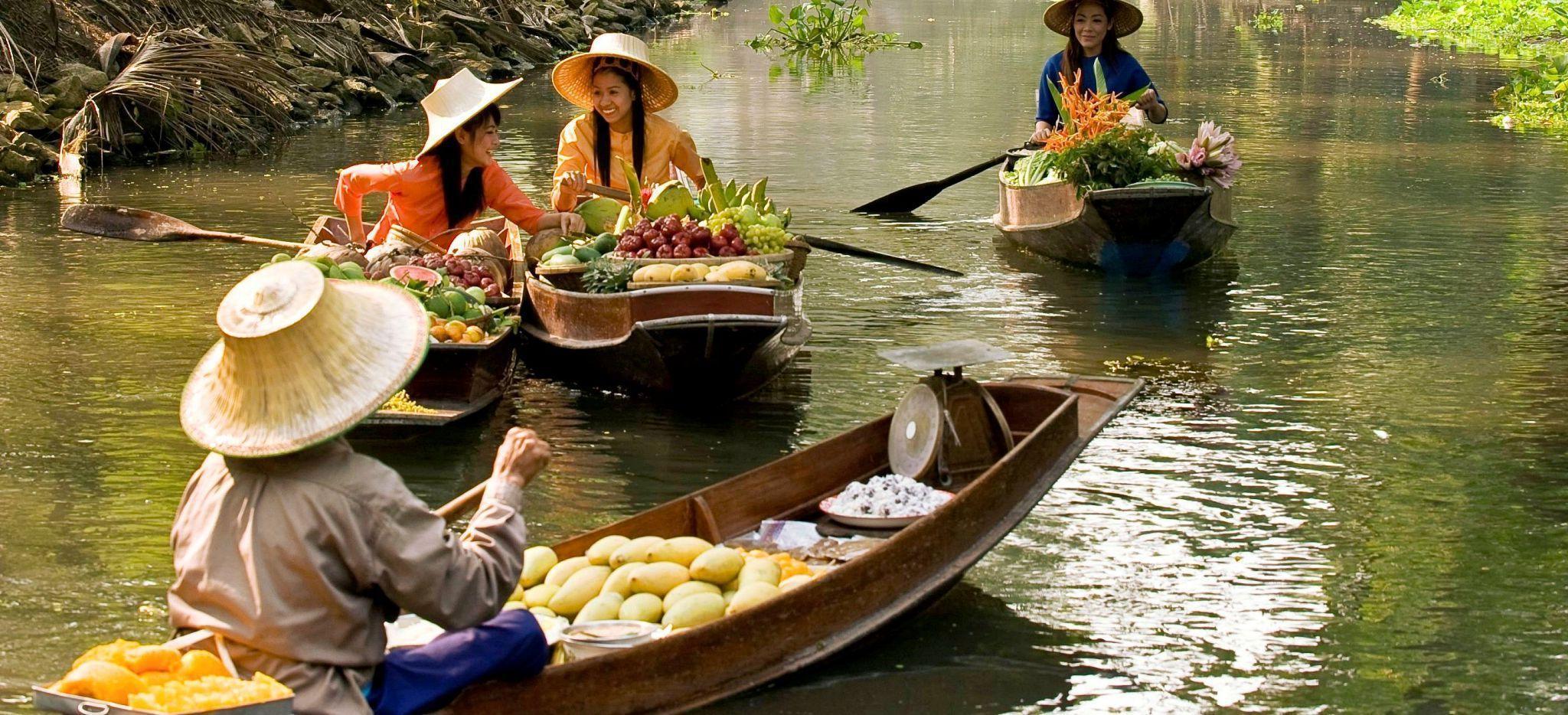 Frauen auf kleinen Ruderboten handeln mit Früchten und Gemüse in Thailand