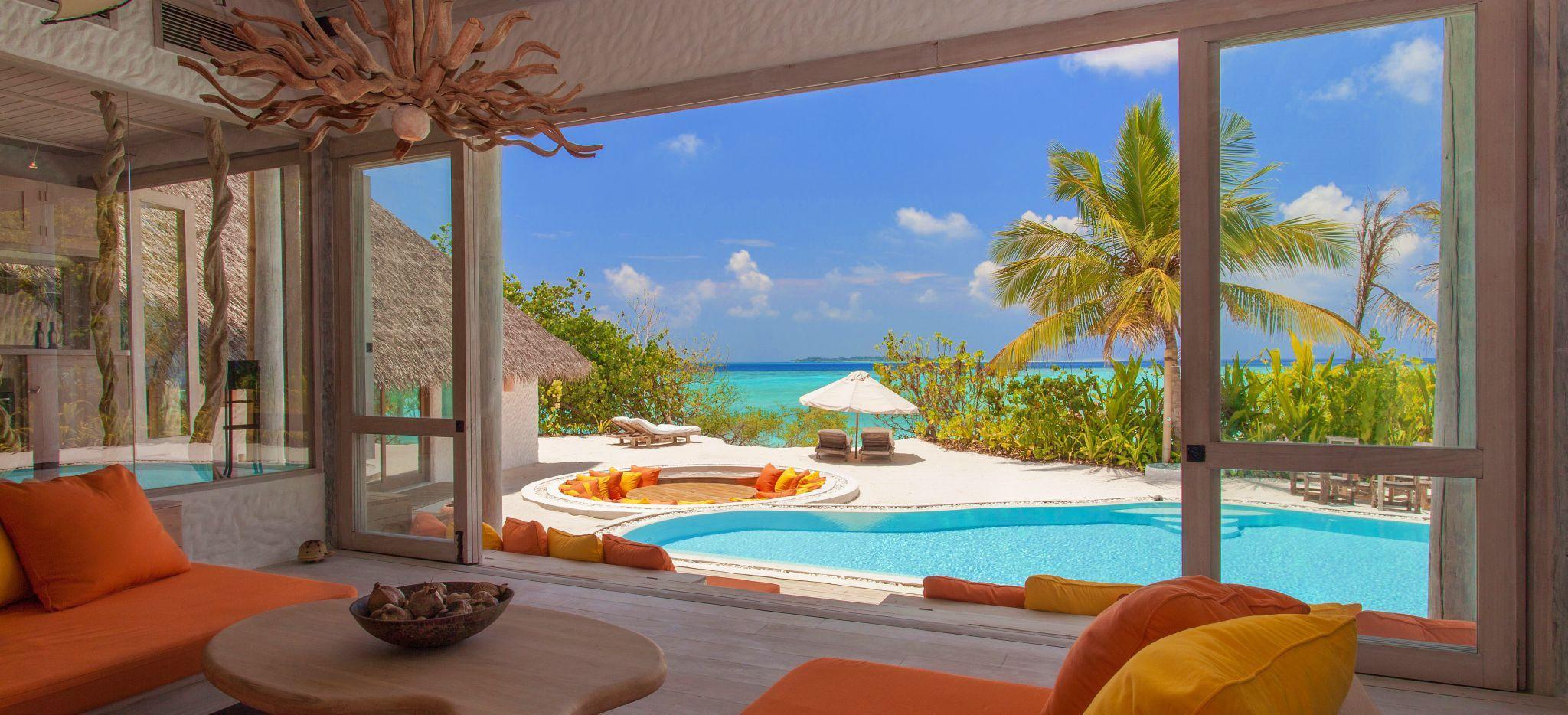 Ein ausladendes Wohnzimmer mit Blick auf einen privaten Pool und Strandzugang im Hotel Soneva Fushi auf den Malediven