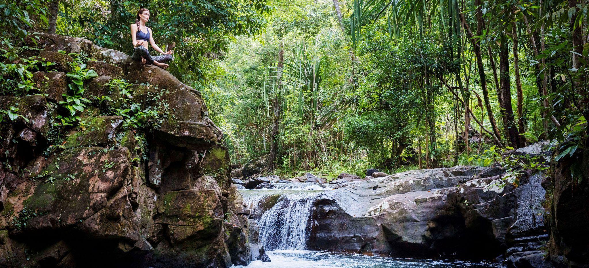 Eine Frau meditiert an einem Wasserfall am Crystal Creed nahe dem Hotel Datai Langkawi in Malaysia