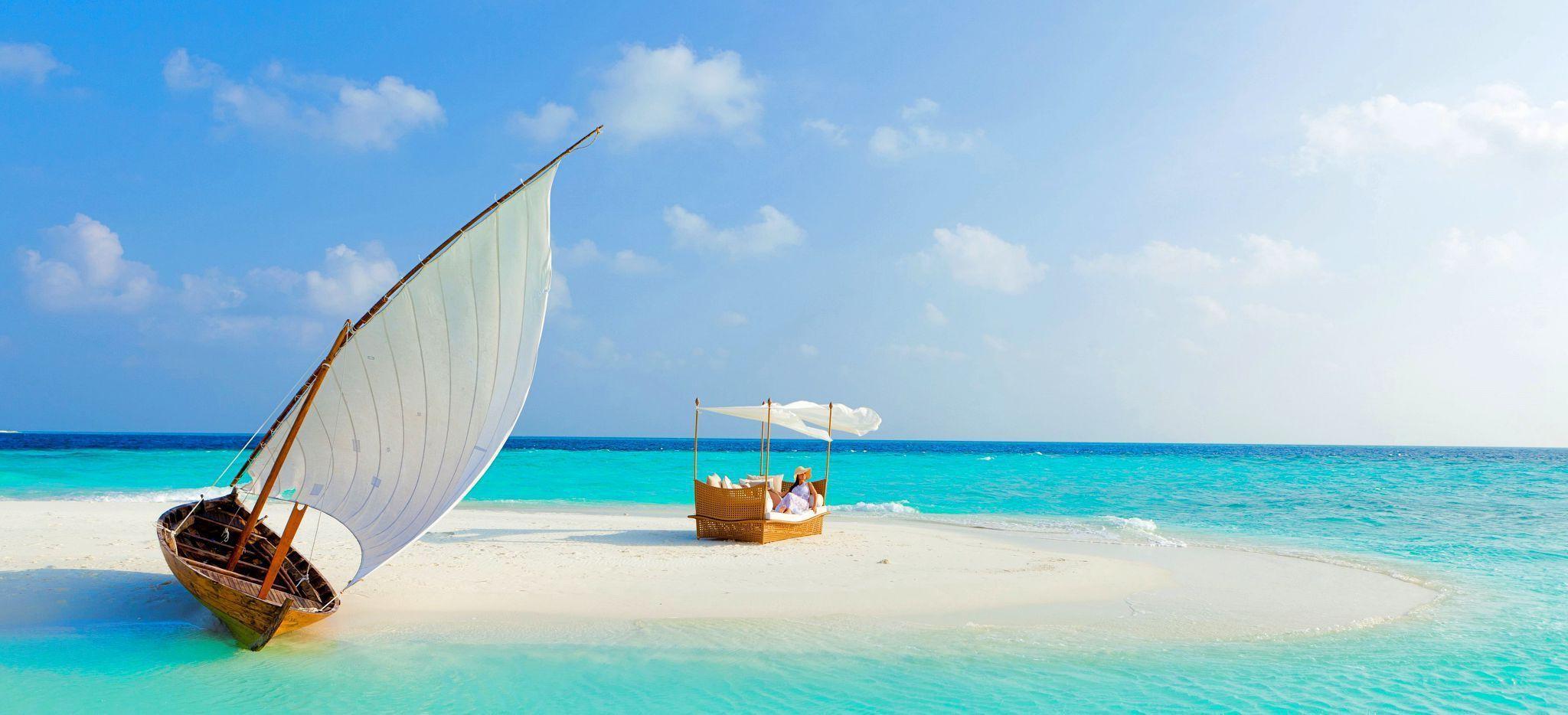 Frau sitzt auf einem Sonnenstuhl auf eine Maledivischen Sandbank, neben ihr liegt ein traditionelles Segelboot auf dem Sand