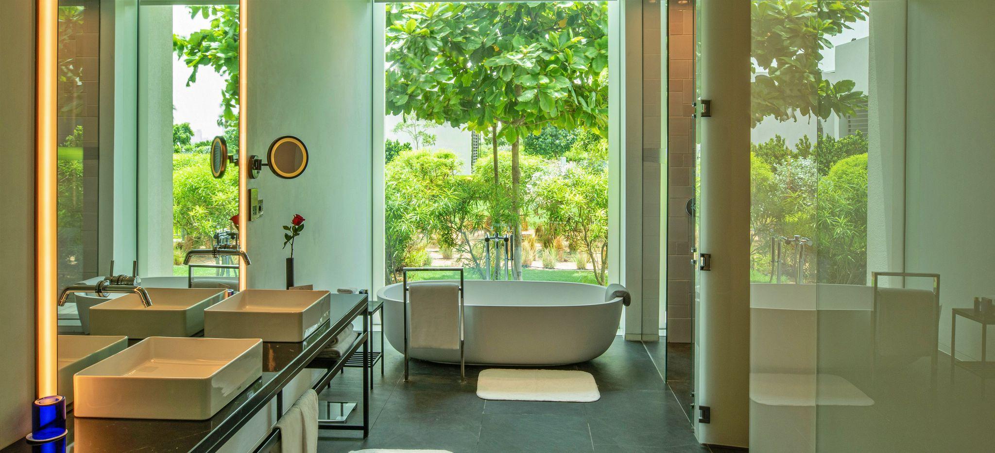 Ein Badezimmer mit Badewanne und Glasfront mit Blick auf den Garten