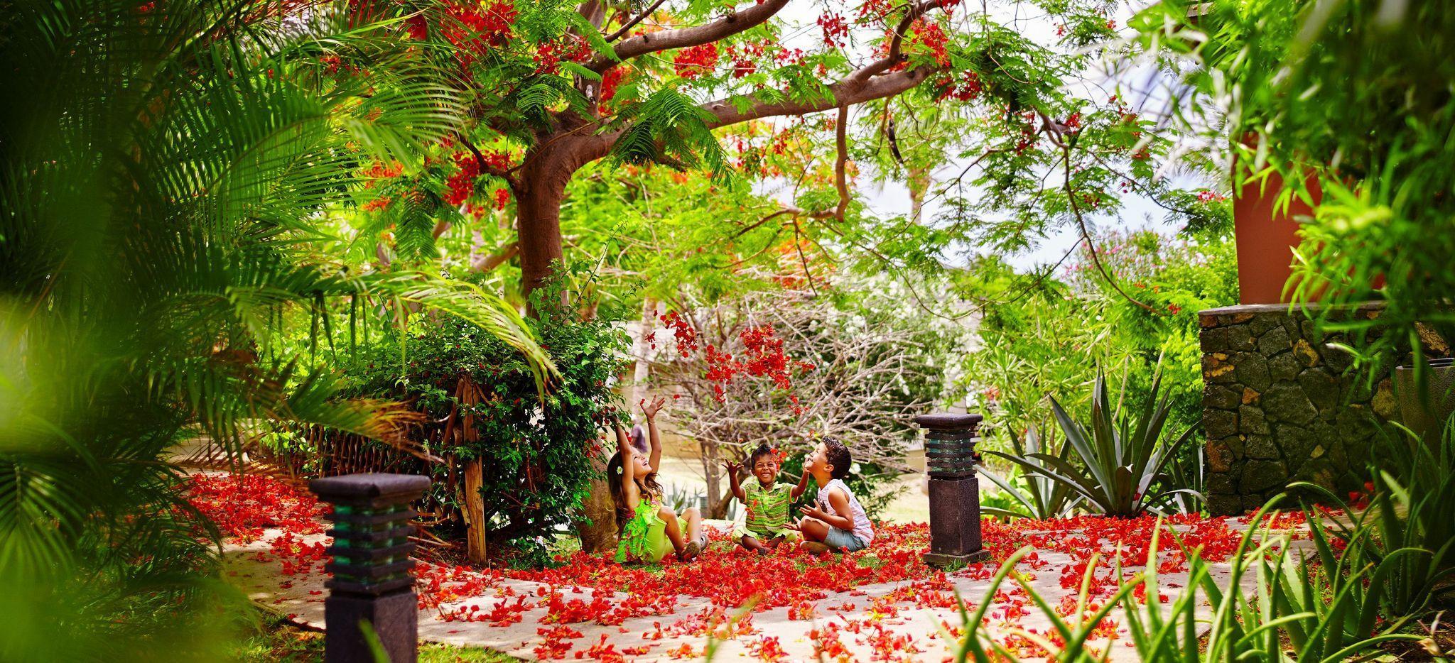 Kinder spielen mit roten Blüten im Garten des Hotels Iloha