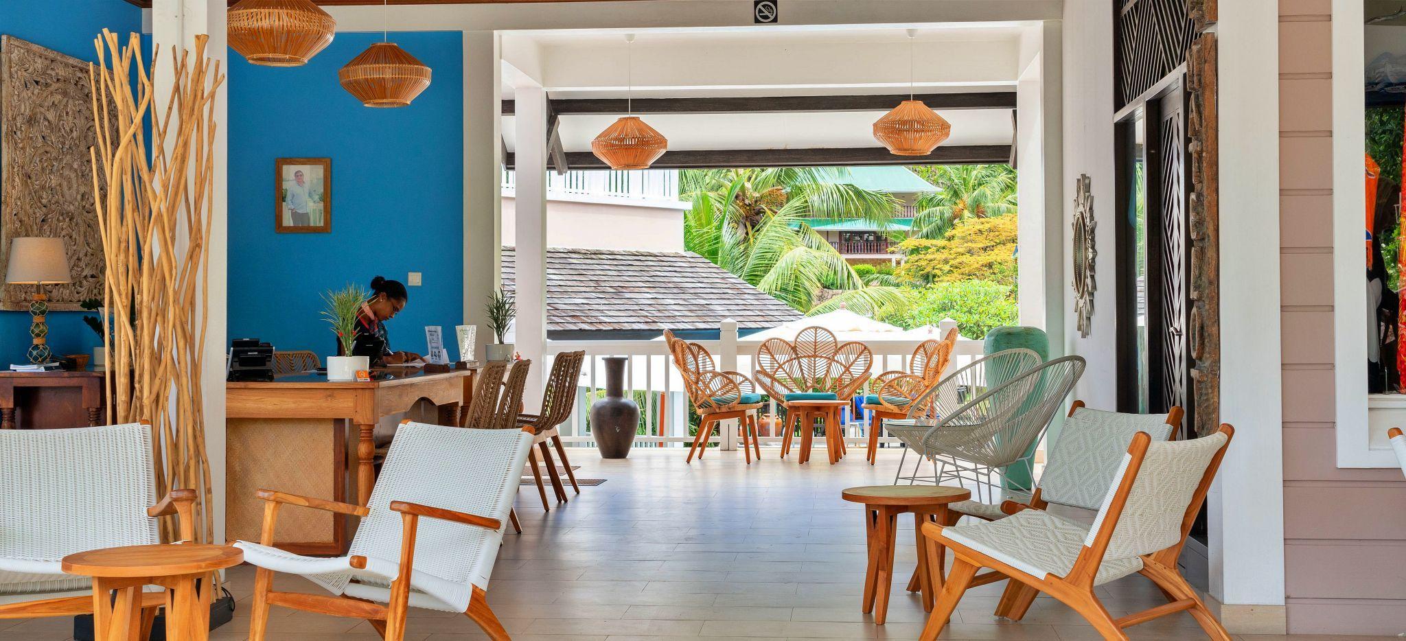 Eine Hotelrezeption mit mehreren gemütlichen Sitzecken, hell erleuchtet. Im Hotel L'Archipel auf den Seychellen