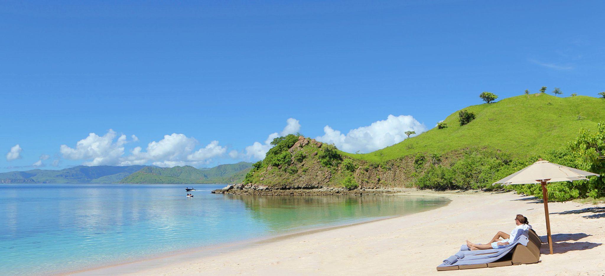 Strandliegen am Strand, Sonnenschirm, Meer und Grün, Indonesien