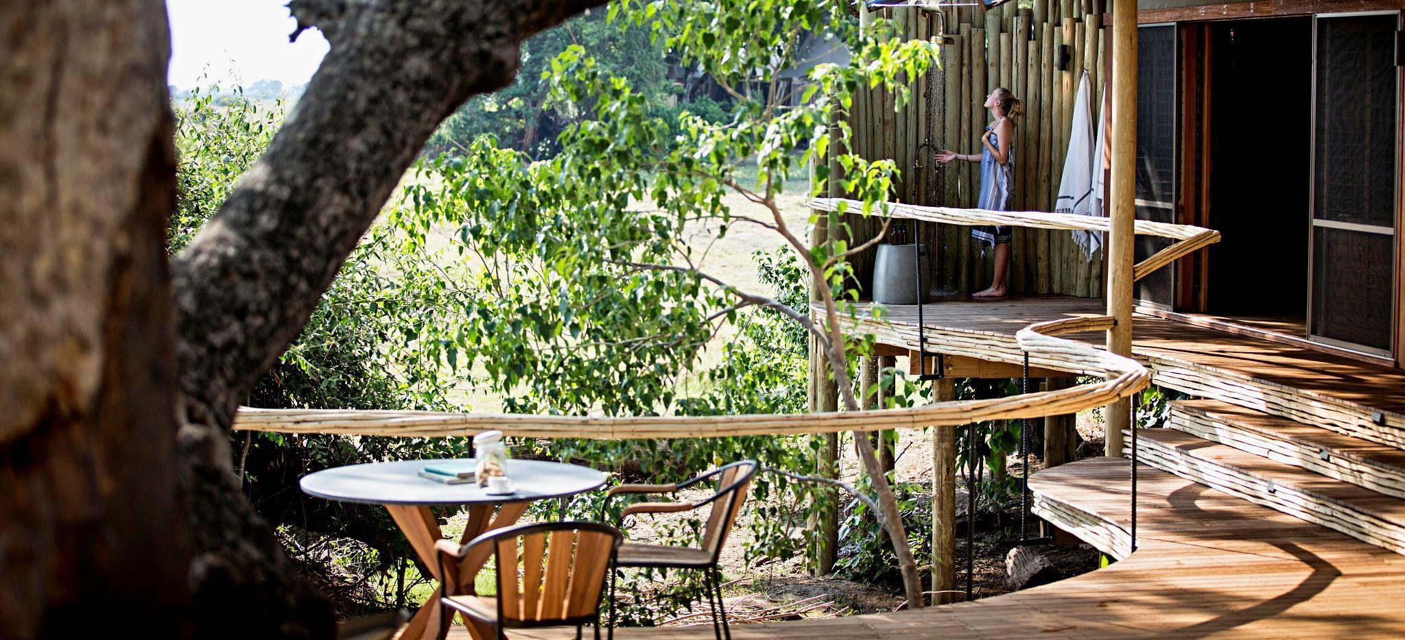 """Eine Frau duscht auf der Terrasse ihres Hotelzimmers in der Safari-Lodge """"Little Mombo"""" in Botsuana"""