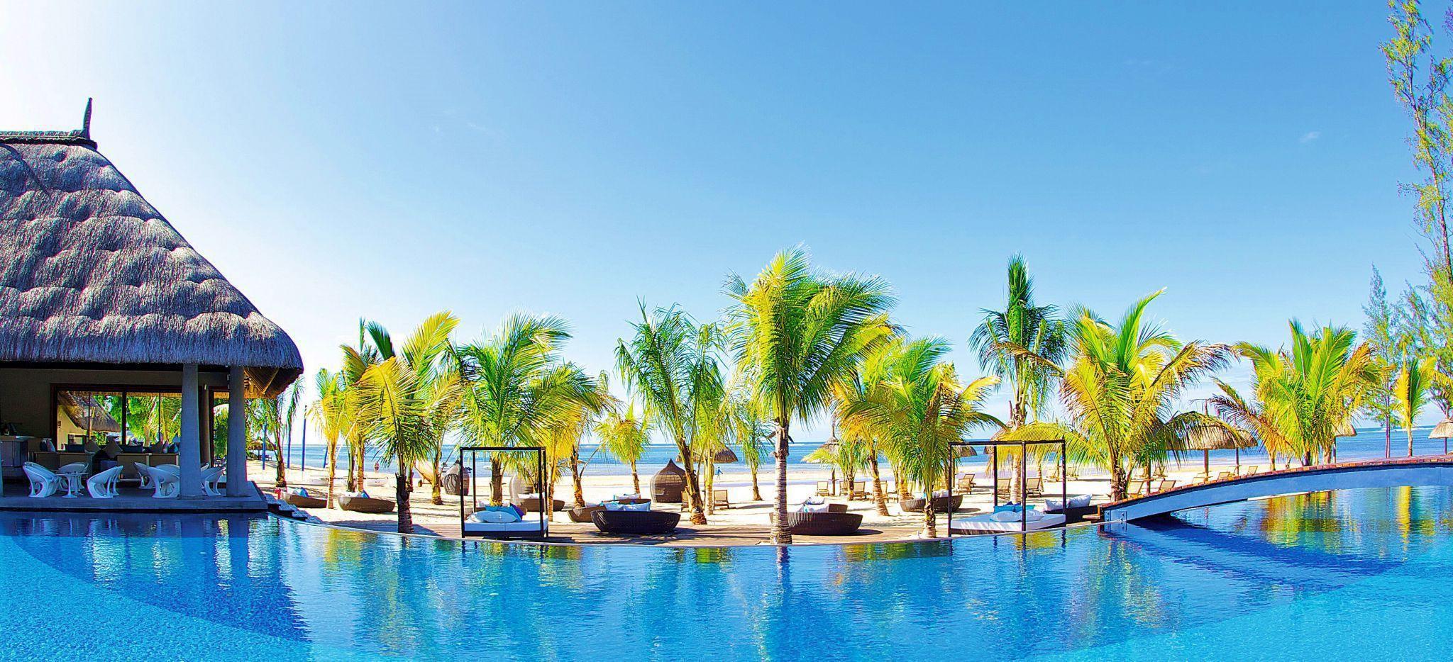 Ein Pool mit dekorativen Palmen und dem Strand und Meer direkt dahinter