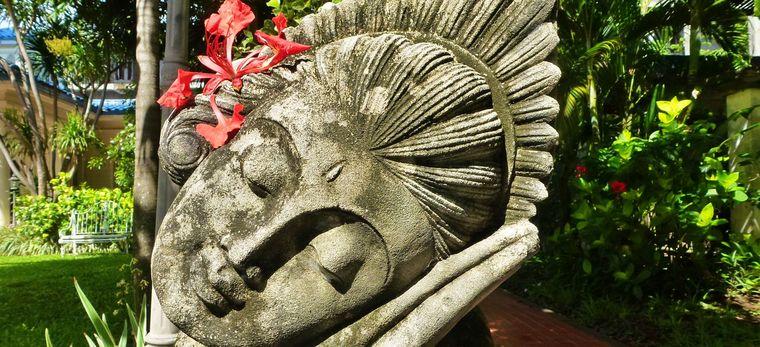 Kopf einer Statue einer Balinesischen Tänzerin, mit echter Blume hinter dem Ohr
