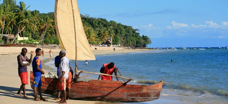 Vier Männer bereiten ein traditionelles Segelboot am Strand von Ambatoloaka auf Madagaskar vor
