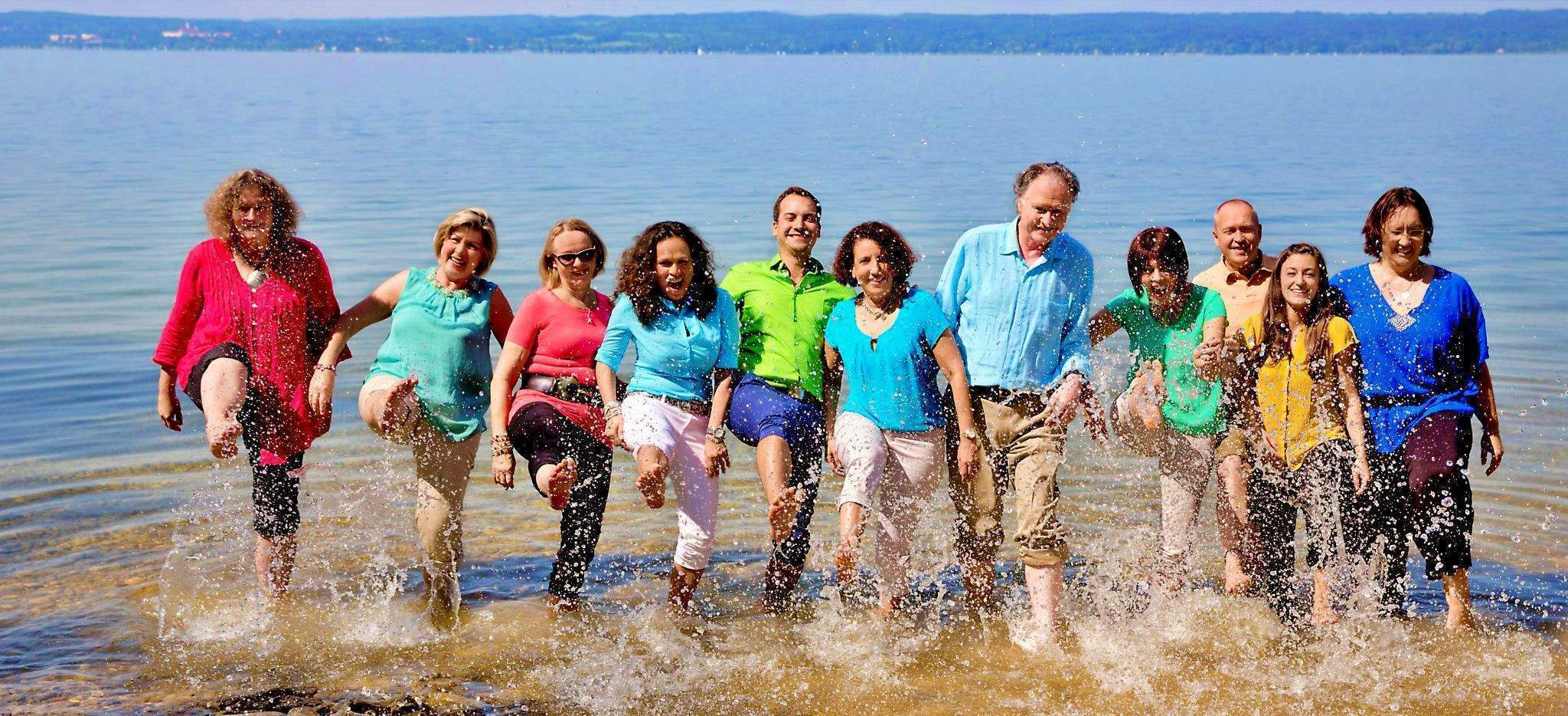 Das Team von Trauminsel Reisen im Ammersee, in bunter Kleidung, treten Wasser in die Luft